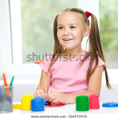 Little girl is having fun while playing with plasticine - stock photo