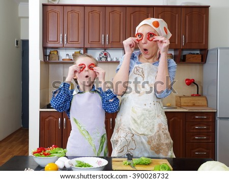 little girl is having fun with  her mother at kitchen - stock photo