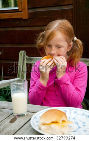 Little girl is having lunch with bread and milk - stock photo
