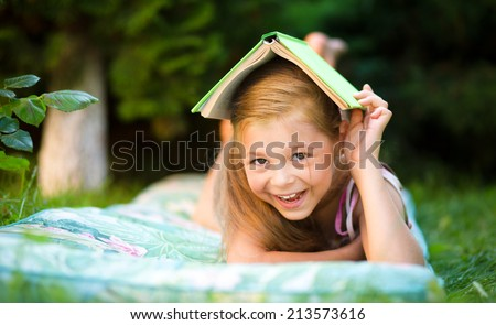 Little girl is hiding under book while laying on green grass - stock photo