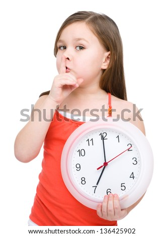 Little girl is holding big clock and showing hush gesture, isolated over white - stock photo