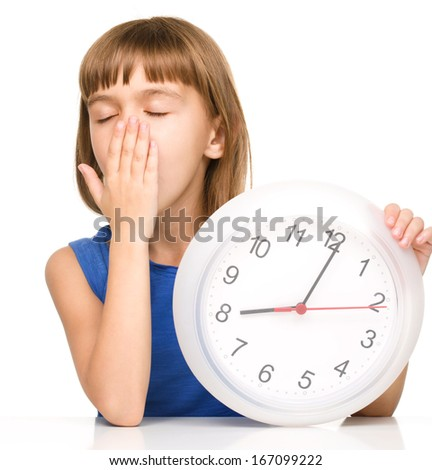Little girl is holding big clock while yawning, isolated over white - stock photo
