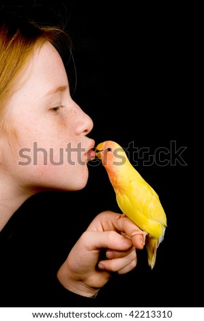 little girl is kissing lovebird on black background - stock photo