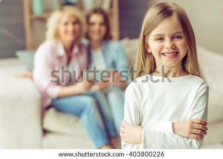 Little girl is looking at camera and smiling, in the background her mom and granny are using a tablet while sitting on sofa at home - stock photo