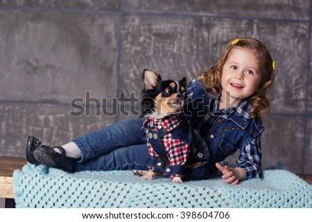 Little girl is lying with chuhuahua dog - stock photo