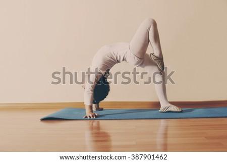 little girl is making gymnastic position indoors - stock photo