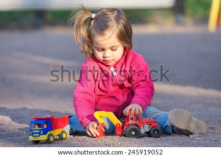Little Girl is playing with her toys at playground - stock photo
