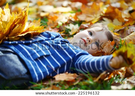 Little girl is playing with maple leaves - stock photo