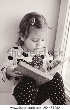 little girl is reading a book near the window - stock photo