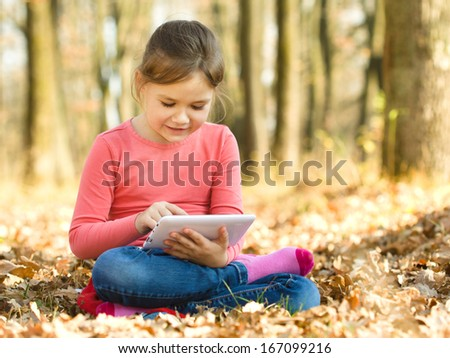 Little girl is reading from tablet while sitting on yellow autumn leaves, outdoor shoot - stock photo