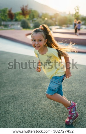 little girl is running and smilling in the park - stock photo