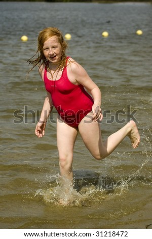 little girl is running in the water - stock photo