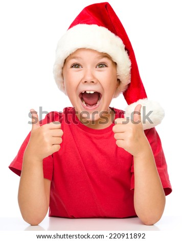 Little girl is showing thumb up sign and wearing santa hat, isolated over white - stock photo