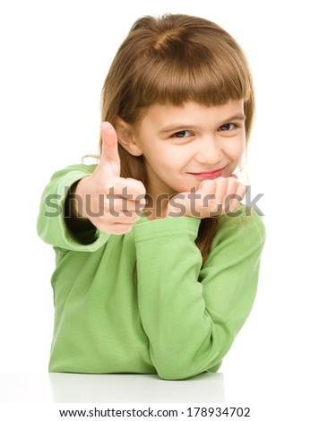 Little girl is showing thumb up sign, isolated over white - stock photo