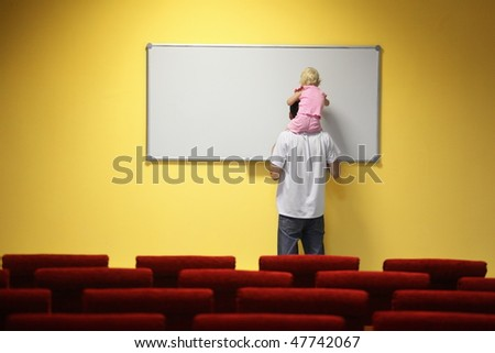 little girl is sitting on father's neck and drawing on a board. chair in out of focus. - stock photo