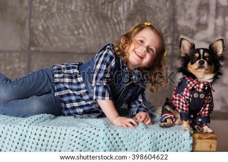 Little girl is sitting with chuhuahua dog - stock photo