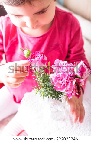 Little girl is smelling the roses. Close up face - stock photo