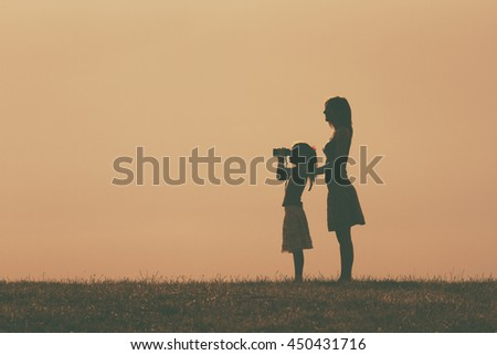 Little girl is standing with her mother outdoor and watching with binoculars nature.Mother and daughter enjoy in nature Image is intentionally with grain and toned. - stock photo