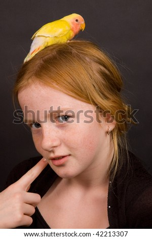 little girl is thinking with lovebird on her head