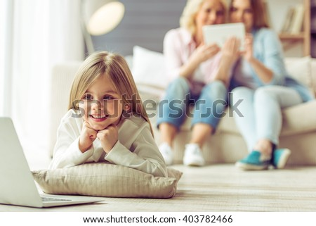 Little girl is using a laptop, in the background her mom and granny are using a tablet while sitting on sofa at home - stock photo