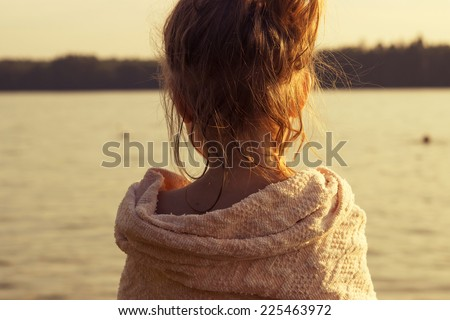 little girl is watching at the sea. Toned - stock photo