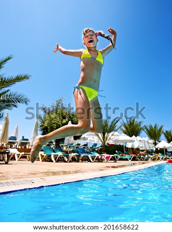 Little girl  jump in swimming  pool. - stock photo