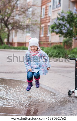 Little girl jumping in muddy puddle and smiling