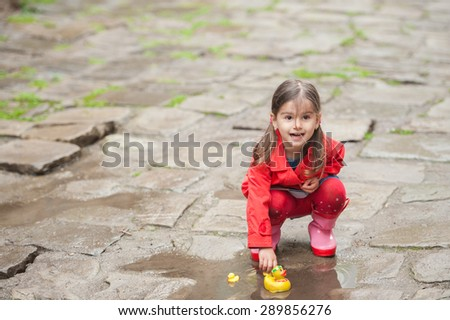 Little girl, jumping in muddy puddles in the park, rubber ducks in the puddle - stock photo