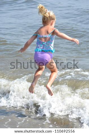 little girl jumping in the ocean - stock photo