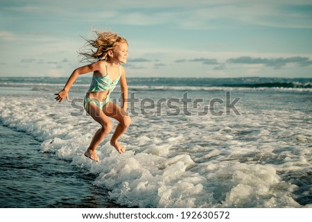 little girl jumping on the beach in the day time - stock photo