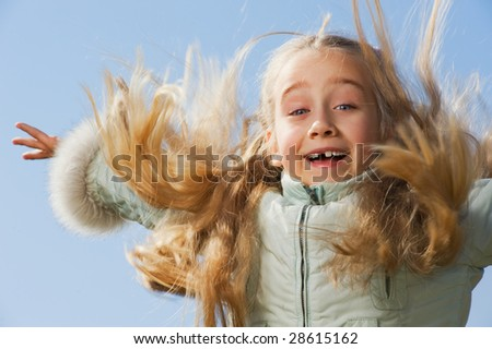 Little girl jumping outdoors - stock photo