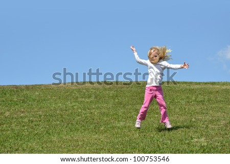 little girl jumping up off the ground - stock photo