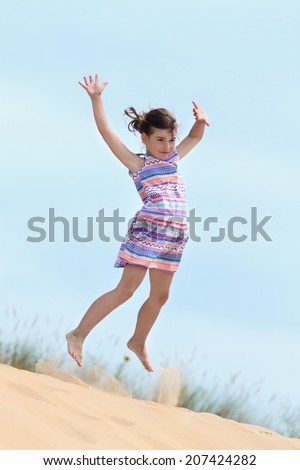 Little girl jumps on sand hill on blue sky background