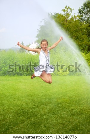 Little girl jumps under spray drops - stock photo