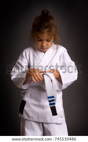 Little girl karatek tie a belt with three deserved stripes