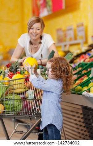 Little girl keeping muskmelon in shopping cart while mother looking at her at grocery store