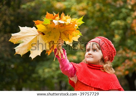 little girl keeps leafs in hand in park in the autumn - stock photo