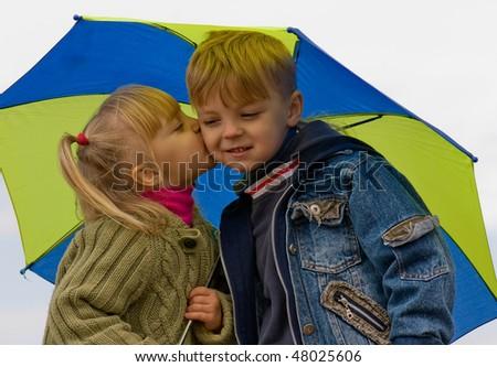 Little girl kiss boy, under umbrella in autumn day - stock photo