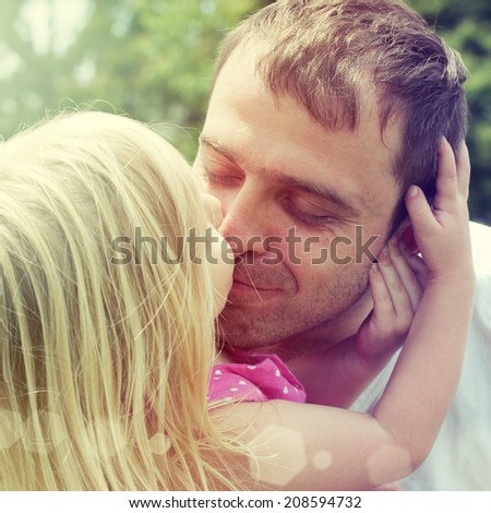 Little girl kissing her father