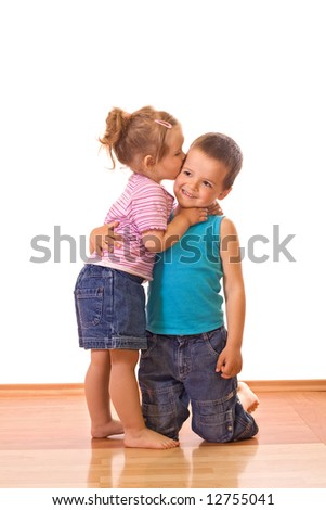 Little girl kissing her older brother on the cheek - isolated