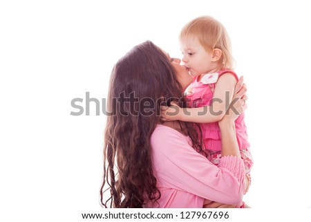 little girl kissing mother on white background in studio