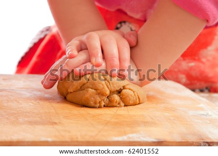 little girl kneading a gingerbread dough, hands only, shallow dof - stock photo