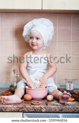 little girl kneading dough in the kitchen