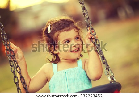 Little girl laughing and swinging on a swing
