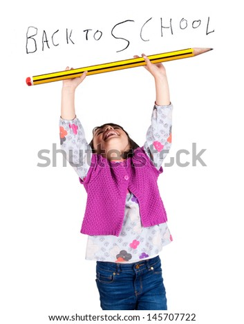 Little girl laughing with arms up holding a big pencil. Hand writing Back to school text. - stock photo