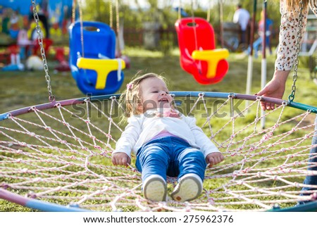 little girl laying in a park nest basket swing - stock photo