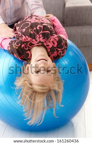 Little girl laying upside down on fit ball, laughing, father holding hands from background.