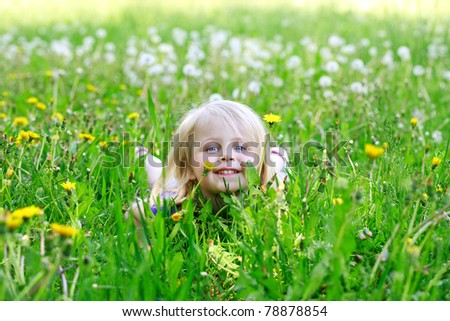 Little girl lays in dandelions outdoors smiling - stock photo