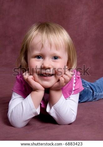little girl lays on dark backdrop for a simlpe portrait - stock photo
