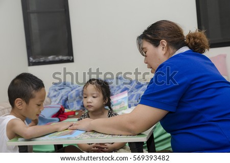 Little girl learning at home with mom